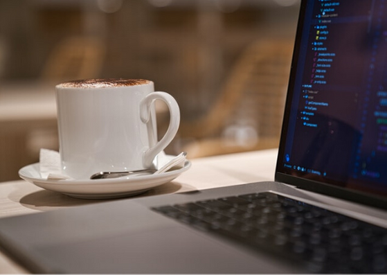 He or she is doing remote work for a company in United States, providing nearshore outsourcing with his or her team. She knows a lot about software development and mobile developmente. She uses a grey computer and shes is drinking coffe with a spoon over his or her wooden desk.
