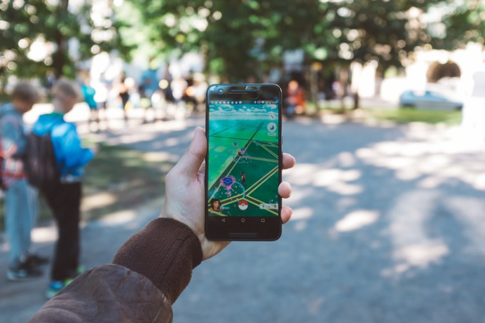 Hand of a boy or men playing PokemonGo the game that offers augmented reality and Geo location in maps with full advanced technology