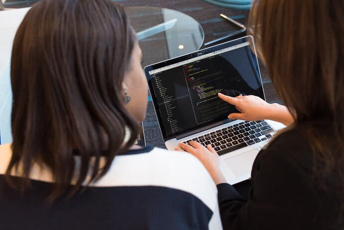 Two women looking at the screen of a black laptop, they are working on a project for a client, the technology they are using is Java. They both work for a remote team.