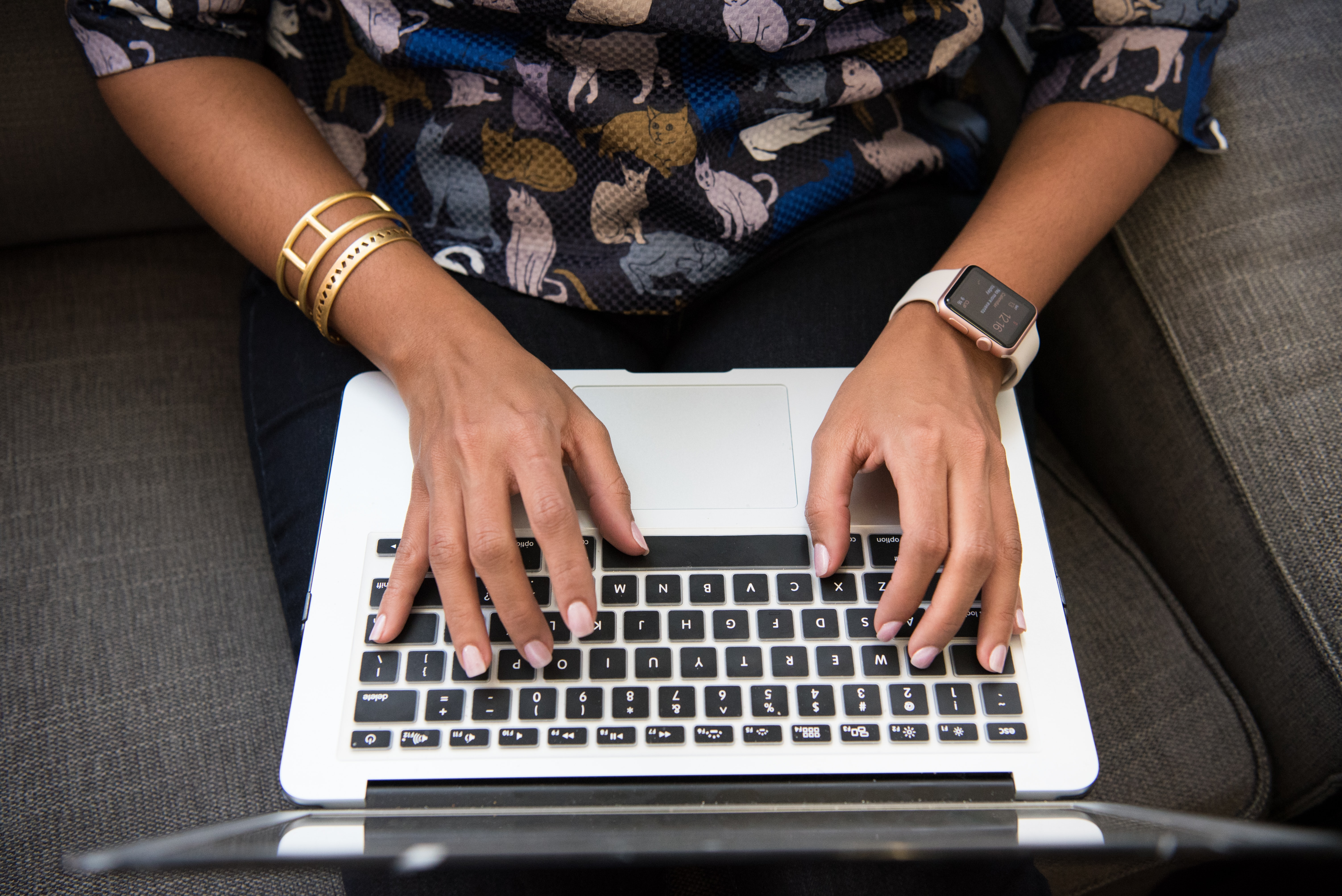 This person is typing on her/his laptop. He/she is working on a client's project, they wanted to add some features to their webpage, and use Java technology. This person works for a remote team and has a bracelet and a watch.