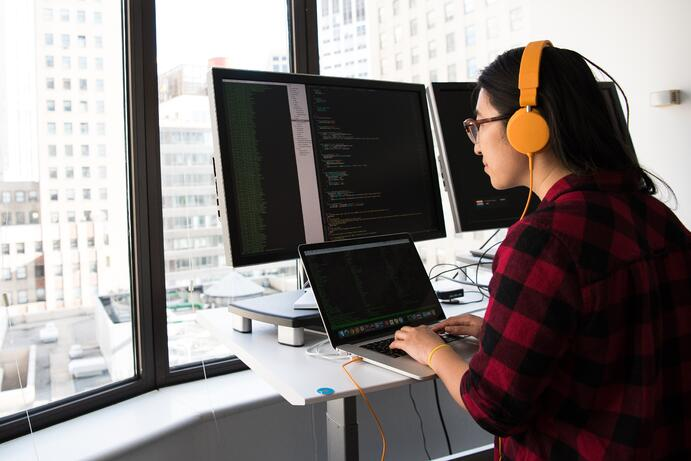 This woman is working for a remote team and she is looking at three screens at the same time because she's working on several proojects at the same time. The client wanted to migrate from Ruby technology to Java technology. She has a red shirt  and yellow headphones.