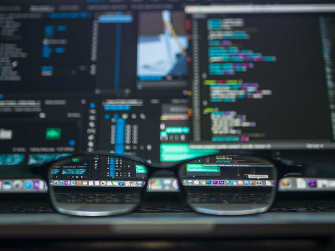 This Java developer wears glasses to better see the screen of his computer, in which he is working on a project for a client. He was asked to develop a website with Java programming language.