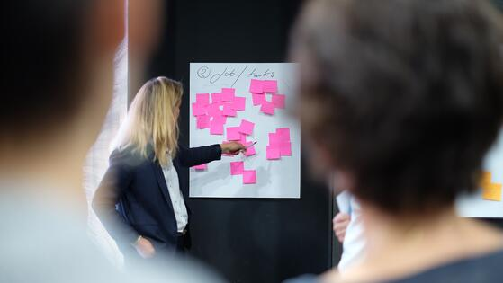 A woman working on a scrum or agile ceremony on the agile methodology using sticky notes, she is blond and there are two teammates listening to her and participating on the event or ceremony. Sticky notes are pink