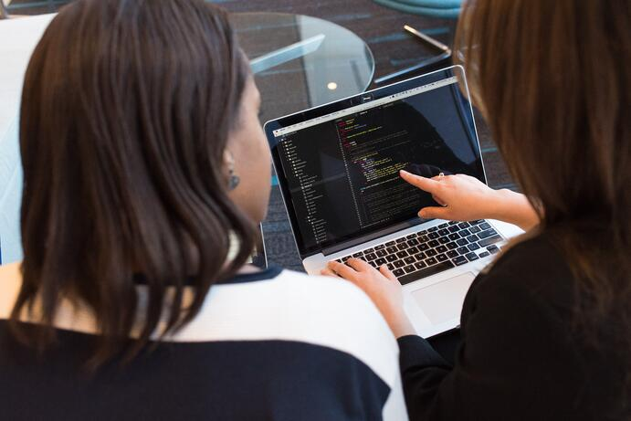 Two women that are teammates working together in an office deciding on the software development estimations in fron of their computer